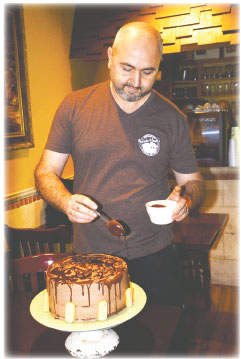 Co-owner and pastry chef Louis Dattilo drizzles extra chocolate onto a chocolate mousse cake he just made for serving at Frankie & Louie's. He also makes special occasion cakes in all shapes and sizes. JANANNE ABEL|WESTMORE NEWS