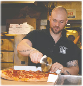 "Co-owner Kevin ""KJ"" Bambara slices a pizza behind the takeout counter at Frankie & Louie's Pizzeria and Restaurant in Port Chester. JANANNE ABEL